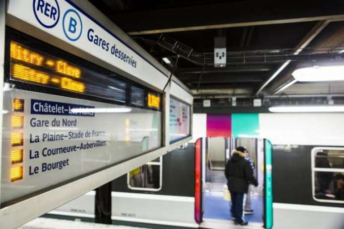 Passengers of Paris suburban line enter train through