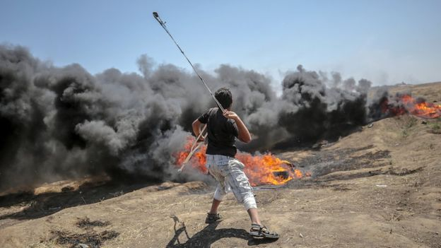 Tension in Gaza as Palestinians begin to bury 58 dead