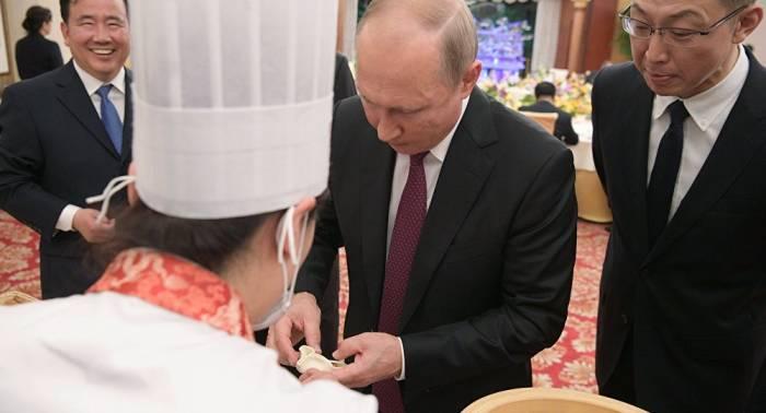 الرئيس الروسي يحضر ويأكل إحدى المأكولات الشعبية في الصين (فيديو)