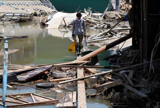 Japan struggles to get help to victims of worst floods in decades