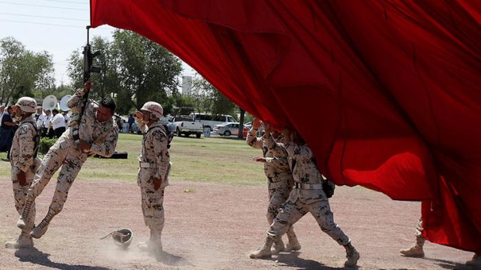 México: Un soldado vuela por los aires tras enredarse con una bandera (VIDEO)