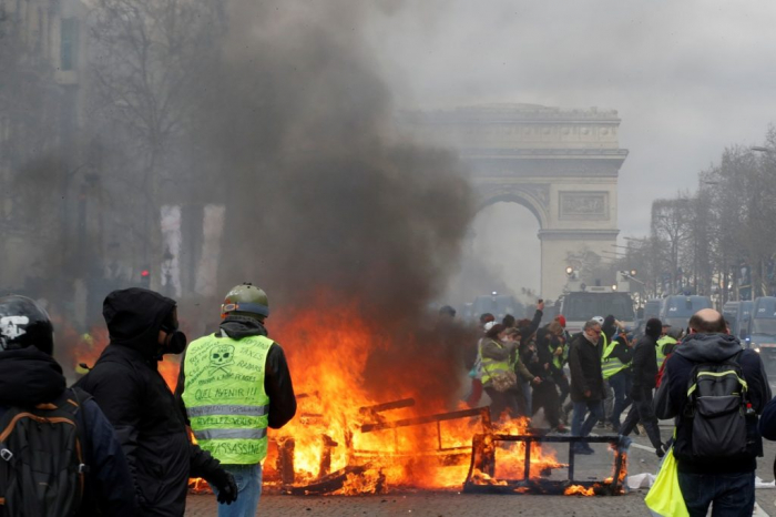 Rioters set fire to a bank and ransack luxury shops in central Paris-  NO COMMENT