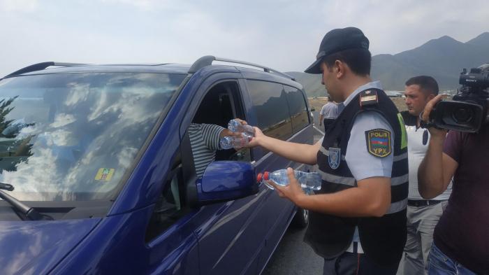 Yol polisi sürücü və sərnişinlərə sərin su payladı - FOTOLAR