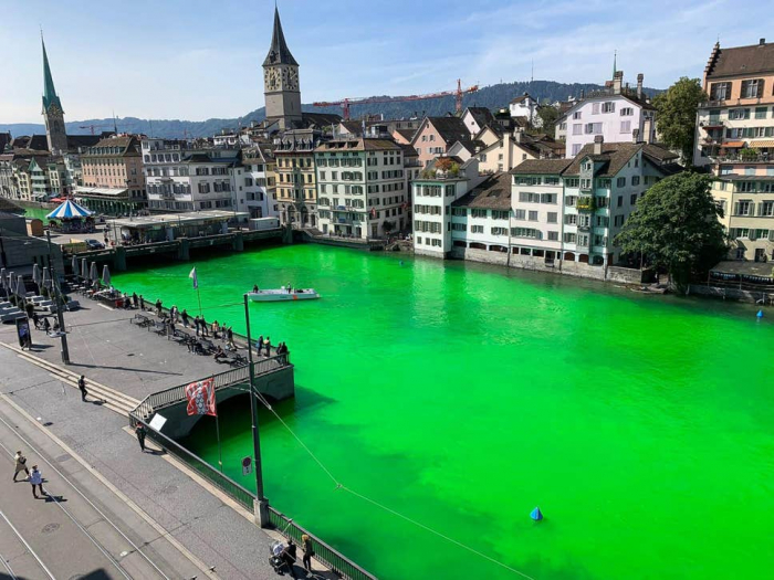 Zurich river dyed luminous green by Extinction Rebellion activists