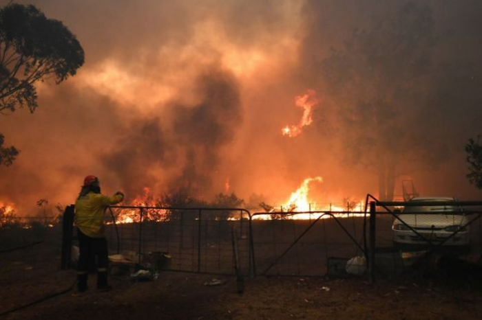 Australian waterbomber helicopter dwarfed by huge wildfire
