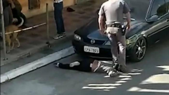 Polizist stemmt Frau Fuß in den Nacken