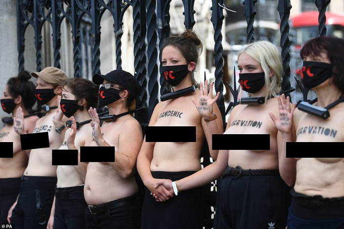 Bare-chested women attach themselves outsideBritain's Houses of Parliament in climate protest