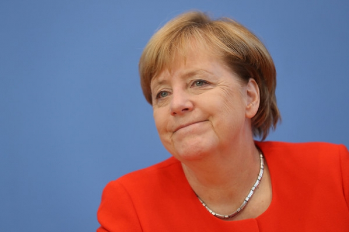 Merkel settles migrant row with allies to pursue coalition