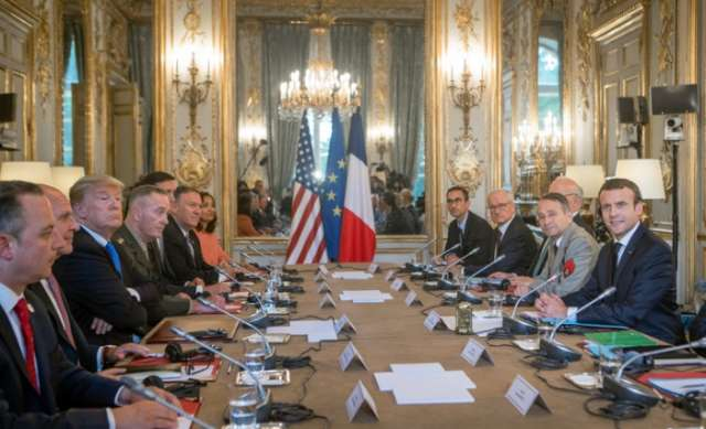 Trump defends his son and plays down differences with French Leader